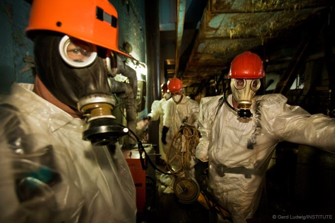 Workers in protective clothing work inside the reactor building