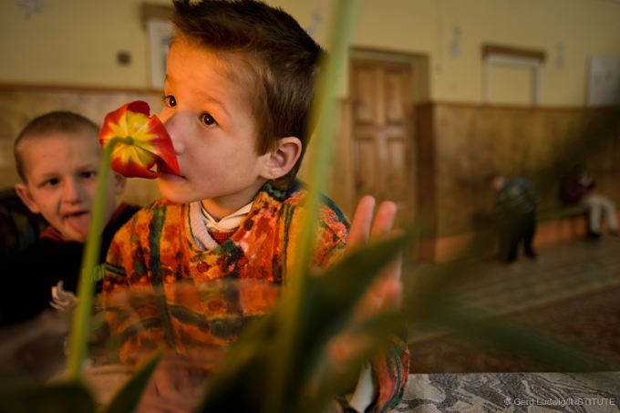 In an orphanage in Belarus, a mentally disabled boy enjoys the scent of a tulip.
